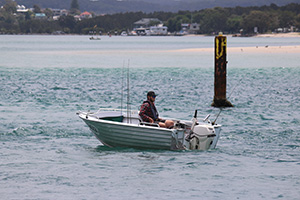Man fishing solo in a small boat on Lake Macquarie